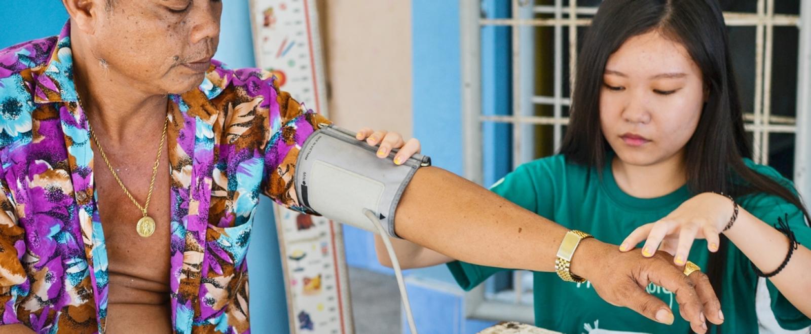 フィリピンに暮らす人々を対象に血圧測定を行う公衆衛生インターン